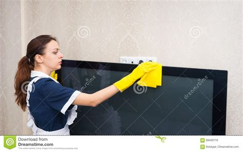 Maid Or Housekeeper Cleaning A Television Set Stock Photo