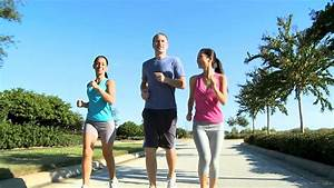 Young Couple Keeping Fit Jogging On Suburban Road Stock ...