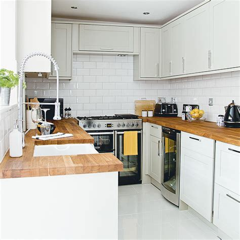 White kitchen with wooden worktops and metro tiles   Ideal