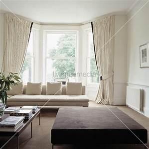 Cremefarbenes sofa und vorh nge vor dem erkerfenster in for Moderne wohnzimmer vorhänge