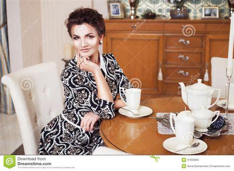 femme du chambre femme hardie riche de brune dans la robe élégante se
