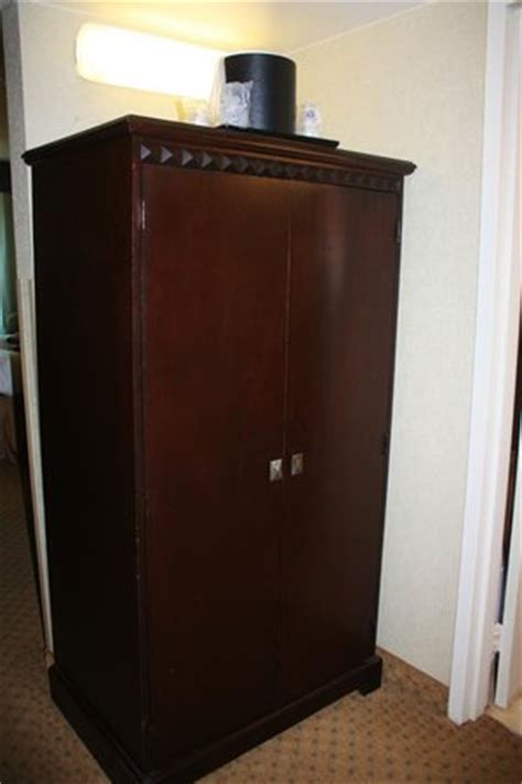 closet with ironing board iron and safe inside picture