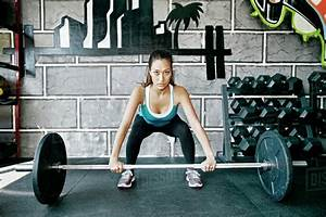 Mixed Race Woman Lifting Weights In Gym - Stock Photo