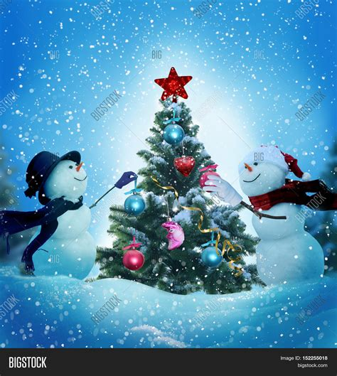 snowmen decorating christmas tree image photo bigstock