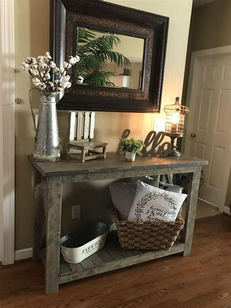 sofa table silver pitcher  stems  bottom left shelf