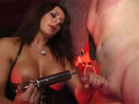 Wild busty mistress in a latex corset whipping her roped ...