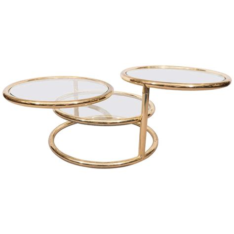 Shows wear consistent with age and use. Milo Baughman Style Circular Three-Tier Swivel Coffee Table in Polished Brass at 1stdibs