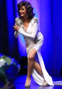 Joan Collins oozes glamour in a plunging white gown at the